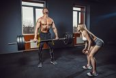 Fit Woman Motivates Man While He Doing Deadlift With Heavy Barbell. Man Lifting Barbell Opposite Win poster