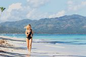 Young Beautiful Girl In Black Swimwear Jogging On The Blue Beach poster