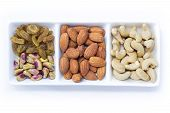Dried fruits and variety of nuts in a bowl on the white table background, such as almonds, raisins, cashews, and pistachio. with copy space for your text.
