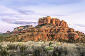The setting sun paints the sky and rock formations of Sedona, Arizona including Cathedral Rock to the right.