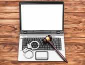 Laptop With Blank Display, Handcuffs And Gavel On Wooden Table. poster