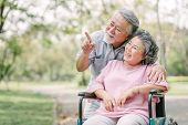 Happy Asian Senior Couple Smiling Outside In The Park While Woman Sitting In Wheelchair poster