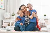 Mother and her children playing together. Mom and girls in Superhero costumes. Mum and kids having f poster