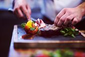 closeup of Chef hands in hotel or restaurant kitchen serving beef steak with vegetable decoration poster