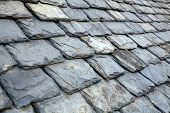 Aged weathered grey slate tile roof in Scotland UK poster