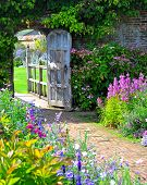 stock photo of gate  - Very old english garden gate leading into flower garden.
