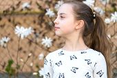 Little Girl On Floral Blossom In Spring. Child With Blossoming Flowers Outdoor. Beauty Kid With Fres poster