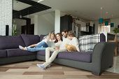 Smiling Parents With Kids Having Fun With Laptop In Cozy Living Room Interior, Couple With Children  poster
