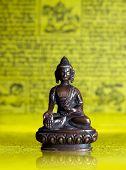 pic of padmasana  - Bronze Buddha sitting in padmasana at yellow Tibetan flags - JPG