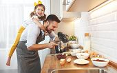 Happy Family In Kitchen. Father And Child Daughter Knead Dough And Bake The Biscuits Together poster
