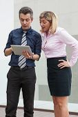 Surprised Male And Female Business People Browsing On Tablet Computer Outdoors. Businesspeople Stand poster