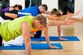 Grupo de cinco personas está haciendo ejercicios en el gimnasio en colchonetas de gimnasia