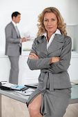 Businesswoman sitting on desk with arms folded