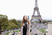 Young Female Person In Grey Coat Standing With Eiffel Tower Background In Paris. Concept Of Travelin poster