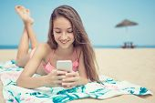 Pretty Teenage Girl Using A Smart Phone Lying The Beach With The Sea And Horizon In The Background O poster