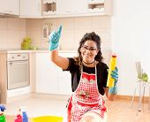 Pretty Young Housewife Holding Bottle Of Disinfectant For Kitchen Floor Cleaning And Showing Thumb U poster