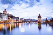 snowfall over beautiful historic city center of Lucerne with famous buildings and lake Lucerne (Vier poster