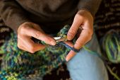 A Woman Knits From Thick Yarn. Handmade Clothes. The Girl Sits On The Couch And Goes In For Her Hobb poster