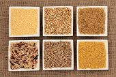 Cereal and grain selection of bulgur wheat, buckwheat, couscous, rye grain and brown and wild rice in white porcelain dishes on hessian sacking background.