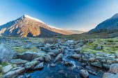 Early Morning Light And Shadow Over Mountains And Snow. Stream  In Foreground And Mountain  Carnedd poster