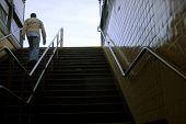 man walking up subway staircase