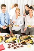 stock photo of picking tray  - Company meeting catering smiling business people eat buffet appetizers - JPG