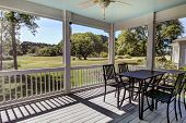Three season screen porch with view out onto golf course and park. poster