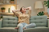 Portrait of beautiful woman resting on sofa at home poster