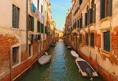 Long And Narrow Canal With Emerald Water Between Ancient Buildings. Boats Moored Near Walls. Picture poster