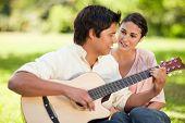 Man ein Lied auf der Gitarre spielen, während sein Lächeln Freund ihn beobachtet, wie sie beide auf th sitzen