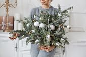 Beautiful Young Woman Holding In Her Hands Handmade Christmas Decoration Made Of Fir Branches, Fir T poster