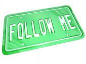 A green metal license plate for a car or other vehicle with the words Follow Me instructing you to watch the example or demonstration of a leader or other manager
