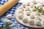 Heap Of Raw Frozen Small Dumplings, Blue Cloth With Dumplings On Wooden Table poster