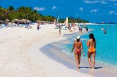 VARADERO,CUBA-MAY 27:Two girls walking and tourists enjoying the beach May 27,2012 in Varadero.With over a million visitors per year,Varadero is the main destination for tourists visiting the island