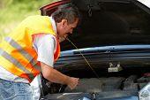 Hombre comprobación de nivel de aceite en una varilla de motor de coche