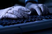 Computer hacker with protective gloves steal data from computer