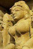 stock photo of kandariya mahadeva temple  - Sculpture of a religious figure decorating the ancient Kandariya Mahadeva Hindu Temple at Khajuraho Uttar Pradesh India - JPG