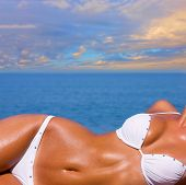 stock photo of sexuality  - The sexual young blonde girl with a beautiful body sunbathes on a beach in a white bathing suit against the sea - JPG