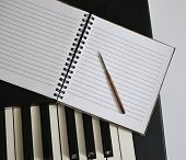 Notebook And Pen On Synthesizer Keys