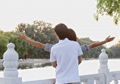 Young couple with arms outstretched by lake