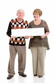 happy senior couple holding white board isolated on white