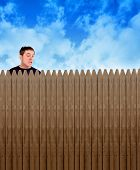 stock photo of envy  - A nosy neighbor is looking over a fence in a backyard at something with shock and surprise on his face for a secret or privacy concept - JPG