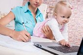 woman with baby in the kitchen working with laptop