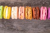 Assortment of French macaroons in rainbow colours, over old wood background with space for your text.
