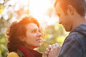 Loving Couple In The Park Looking At Each Other In The Sunlight On The Bokeh Background