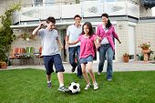 picture of football  - Cute kids playing football with their parents at backyard