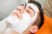 stock photo of face mask  - Therapist applying a face mask to a beautiful young man in a spa using a cosmetics brush - JPG