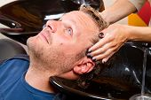 stock photo of beauty parlour  - Washing man hair in beauty parlour hairdressing salon - JPG