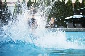 Young man jumping into pool with water splashing all around him
