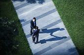 Aerial view of two businessmen shaking hands on sidewalk